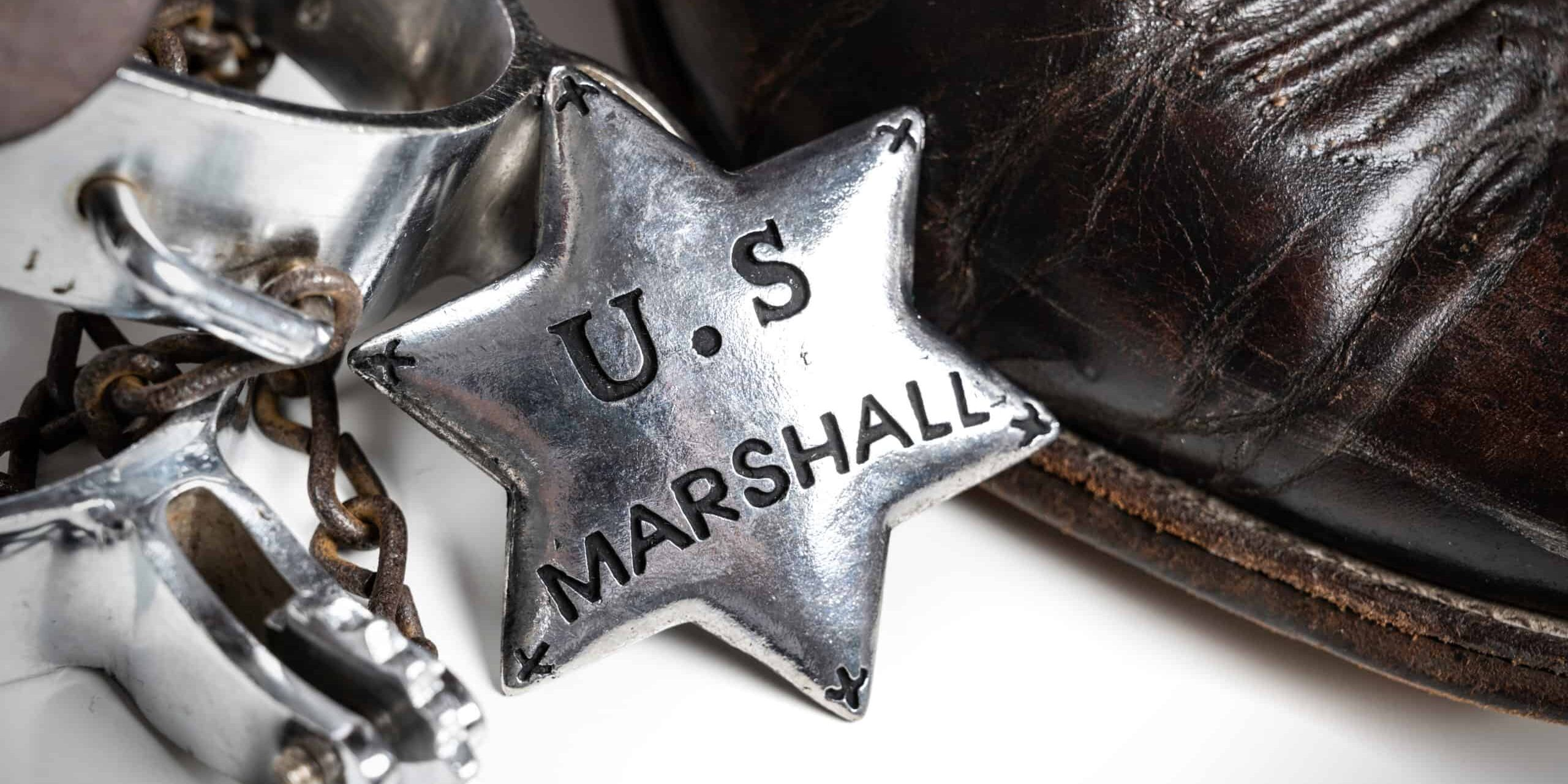 A group Of items old West themed items including United States Marshalls badge with cowboy boots and spurs